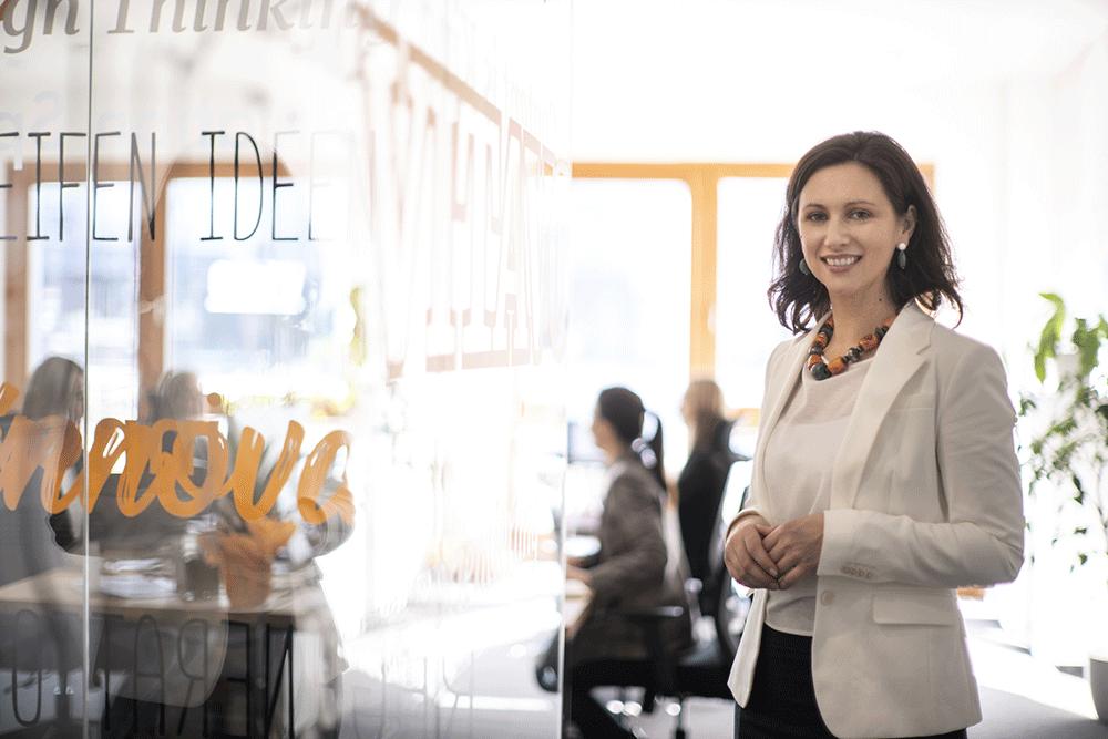 weiblicher ceo steht lächelnd im büro und im hintergrund arbeiten mitarbeiterinnen