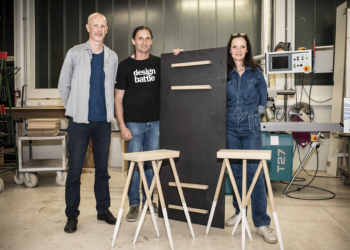 Erwinn Bauer, BB Coyle und Tischler stehen neben ihrem Designentwurf.
