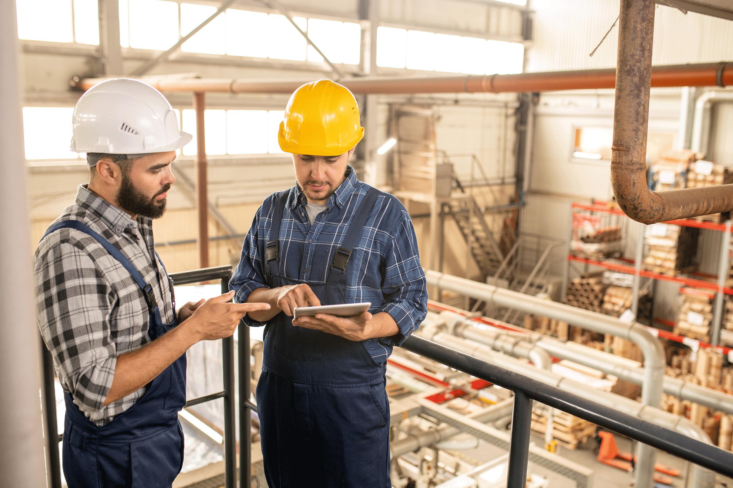 Zwei junge Ingenieure einer großen Fabrik besprechen die Reports in der JOYSTICK Software.