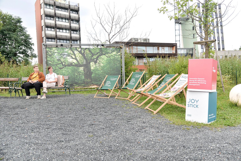 Zwei Frauen sitzen auf Bank neben Stadt Hartberg Liegestühlen. VITAVO JOYSTICK und Miss Maggie Würfel