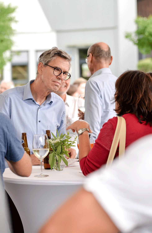 Mann mit Brille unterhält sich mit Frau
