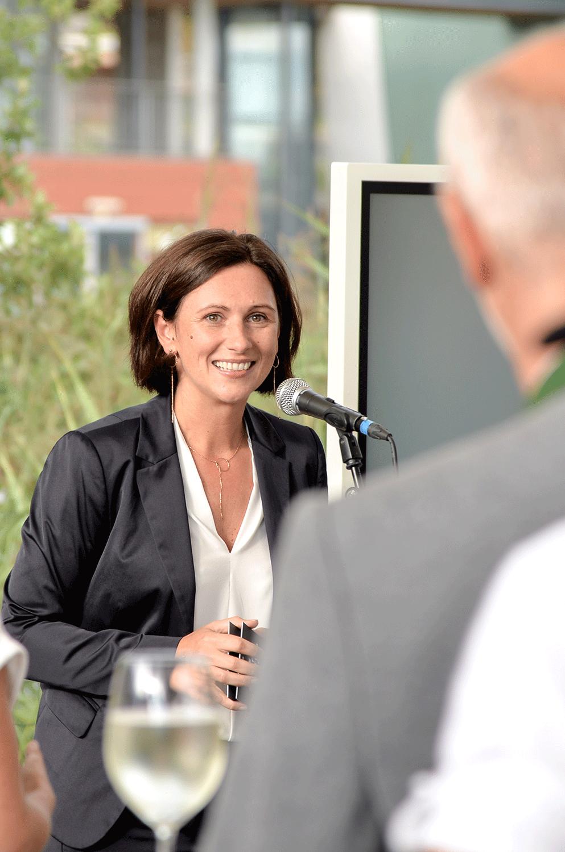 Lächelnde Frau spricht in ein Mikrophon