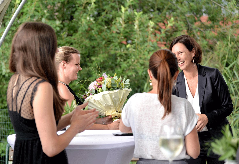 Geschäftsführerin überreicht Frau einen Blumenstrauß