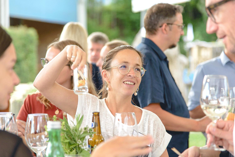 Lachende Frau mit Dessertglas in der Hand