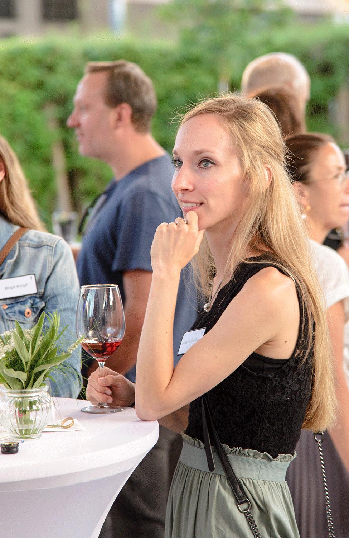Blonde Frau mit Getränk in der Hand hört zu.