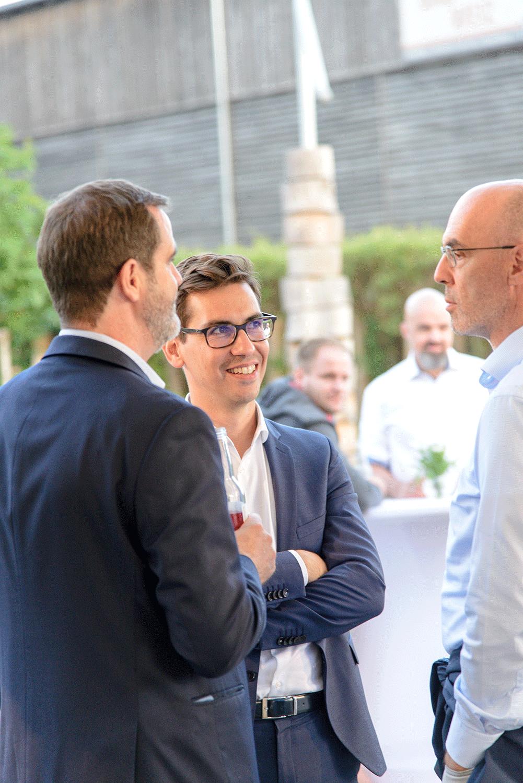 Drei Männer in Business-Look in einem Gespräch
