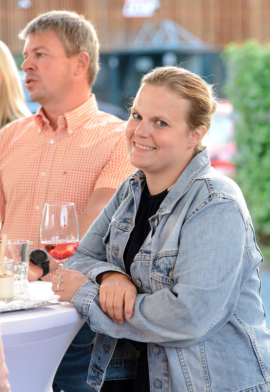 Lächelnde blonde Frau mit Jeansjacke und Getränk