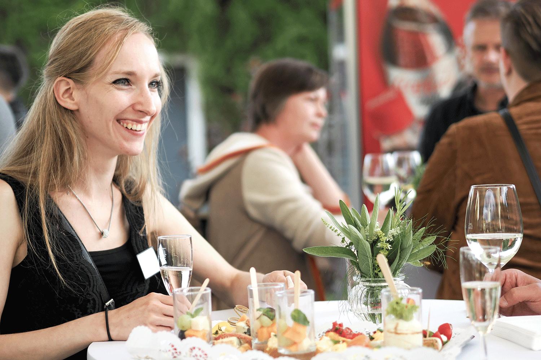 Blonde Frau lacht. Am Stehtisch vor ihr steht Essen.