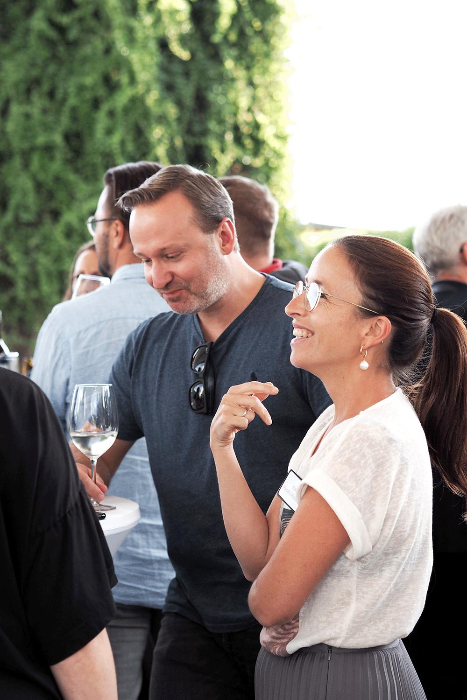 Gut gelaunte Frau unterhält sich mit Mann mit Weinglas